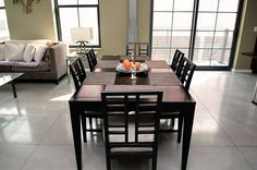 Dining room in a condo with a contemporary and industrial style. Includes concrete floors and floor to ceiling windows.