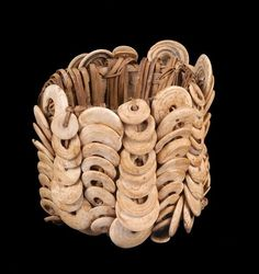 Papua New Guinea ~ East Sepik (province) ~ Ambunti (district) ~ Chambri (sub-district) ~ Aibom (village) | An armband, from the Latmul people, formed with shells wrapped around a rattan frame.  The upward and downward movement of the disc recalls the ripples of the Sepik river | Mid 20th century.