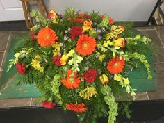 Fall sympathy casket spray by Hartman's Flowers. Funeral flowers and arrangements