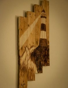 Lighthouse painted using wood stain on a canvas made of pallet wood