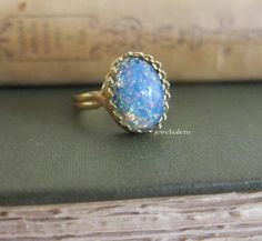 Stunning fire opal ring in high quality setting. Very whimsical and unique.  Ring is adjustable!  Stone measures 10x14mm.    You can choose from gold
