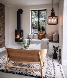 The natural tones and stripped-back chair in this Scandinavian-inspired room are built around a picturesque window view surrounded by classic log-burner and retro lighting. This would be the perfect living room of comfort in every home.