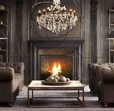 Great Room with a cozy fireplace & rich deep color leather sofas & dark painted  walls with a touch of sparkle in the chandalier.