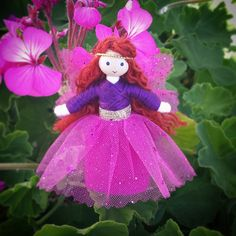 This beautiful little flower fairy is sure to delight any youngster or collector! Dressed in a lovely purple top and pink skirt with a pink glitter mesh overlay and silver belt she looks as though she