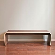 """Dario Antonioni's Botanist Minimal Walnut Bench is a study in clean, simple design. Antonioni rigorously examined the pieces of a typical bench, and reduced them to two essential elements: a bent wood top that transitions into the structural legs, and a center rib for additional stability. And there is no hardware visible anywhere on this beautiful piece—so sit for hours and let your thoughts wander. Features an authentic signature medallion in brushed stainless steel. L 60"""" W 18"""" H 18""""…"""