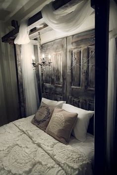 I'm just thinking here...  What about using 2 reclaimed doors on sliding hardware (maybe like barn doors???).  Then putting the bed directly in front of the window, using the barn doors to completely close the window like a window treatment and a headboard all in one???  Then the doors could slide open behind the bedside chests during the day. Thoughts?