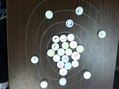 Making atom models on the desk with dry erase markers and bottle caps! Good idea!
