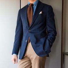Something as simple as teaming a dark blue coat with tan casual trousers can potentially set you apart from the crowd. Shop this look on Lookastic: https://lookastic.com/men/looks/blazer-denim-shirt-chinos/23127 — Blue Denim Shirt — Brown Wool Tie — White Pocket Square — Navy Blazer — Khaki Chinos