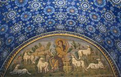 Mosaic of Christ as the Good Shepherd over the entrance of the Mausoleum of Galla Placidia, dating from around 430 AD. This image was common in the Roman catacombs of earlier centuries, but there are important developments to be seen in this version. Instead of being shown as a typical countryman, this Good Shepherd has a large golden halo, wears a royal purple mantle over a golden tunic, and holds a tall cross.
