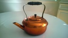 Have a cuppa from the copper!  This vintage teapot is perfect for serving up your favorite brew. It has a beautiful sunset glow when sunlight hits it.  I believe this piece to be made of copper. The handle is wooden.  Holds about 12 cups. Without the handle up (like in the second photo), the pot is about 8 inches tall. It is also about 8.5 inches in diameter at its widest.  The kettle is in good vintage condition. It has typical cosmetic wear and tarnish. There is a small dent in the lid…