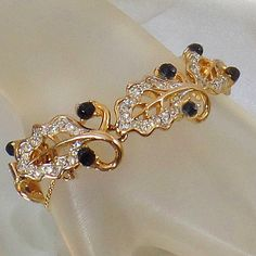 This #vintage Kramer rhinestone bracelet is beautiful.  It features a gold plated bracelet with gold leaves filled with clear rhinestones and accented with black rhinestone ... #ecochic #etsy #jewelry #jewellery