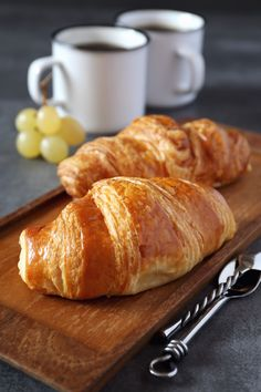 Two fresh croissants and cups of coffee - Two fresh croissants and cups of espresso. Selective focus