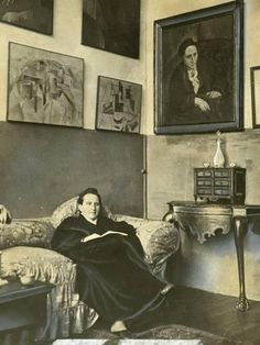 Gertrude Stein sitting on a sofa in her Paris studio, with a portrait of her by Pablo Picasso, and other modern art paintings hanging on the wall behind her. --> Souvenir de l'exposition sur les Stein, collectionneurs et mécènes, au Grand Palais en Henri Matisse, Pablo Picasso, Ute Lemper, Maria Callas, Tilda Swinton, American Poets, Writers And Poets, Modern Art Paintings, Art Moderne