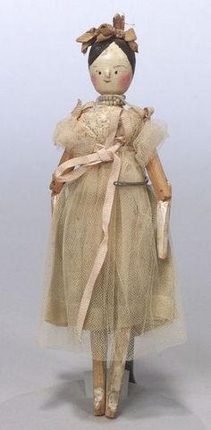 Small Penny Wooden Doll, England, late 19th century, painted features, rosy cheeks, applied nose, black painted hair, peg-jointed body, original organdy and net dress, grosgrain ribbon trim on dress and top of head, ht. 8 1/2 in.