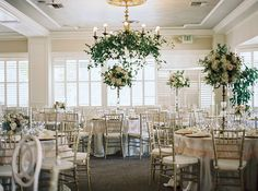 This garden style wedding took the wedding reception indoors, but continued the theme through hanging greenery wreaths for chandeliers and tall floral centerpieces for each table. | Stephanee & Johnathan's Real Wedding by Mariel Hannah Photography from mywedding Magazine #myweddingmag