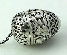 German Pseudo Marked Pull Apart Silver Tea Ball A German egg shaped tea ball marked on the inside lip and pierced with flowers and lattice work. The tea ball pulls apart and the lid is removed by pulling over the chain.