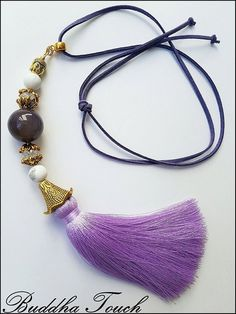 The one and only Buddha Touch Beads Tassel Necklace 'Purple Candy'. It is one of a kind and it is handmade.  Excellent quality.   It is made out of Mate Howlite, Agate and Mountain Crystal, leather strap, silk tassel.  Mountain Crystal brings spiritual and physical connection; Agate can cleanse and stabilize the aura by removing and/or transforming negative energy; Howlite is a stone of wisdom, memory, knowledge and advancement.