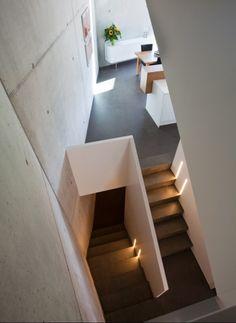 Die ungewöhnlich bergenden Raumformen, die sich über die Geschosse staffeln und Licht von oben erhalten, geben dem Haus fast eine sakrale Anmutung. | L3P Architekten © Vito Stallone, Baar