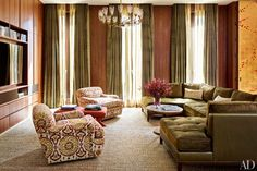 Decorator Laura Santos designed the club chairs (upholstered in a Kravet ikat) and sectional, all made by Dune, that outfit the media room in her Manhattan townhouse