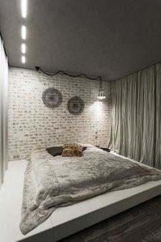 une chambre à coucher élégante en gris clair avec un mur de briques