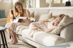 MG 1617. Las hijas de Lorenzo Meazza, responsable de interiorismo de Ikea, en el sofá del estar de su casa tocando la guitarra