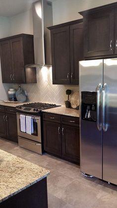 "Simmons Homes: Bailey Plan Kitchen. Vent hood. Herringbone backsplash. 42"" Custom cabinets. Dark Brown. #customkitchens"
