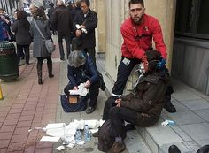 A private security guard helps a terrorism victim outside a metro station in Brussels