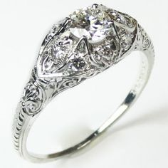 Filigree Fantasy: A flashing antique diamond is enhanced by a liberal sprinkling of glittering accent diamonds, giving the whole ring a dreamy, sugar frosted look. Ca. 1910. Maloys.com