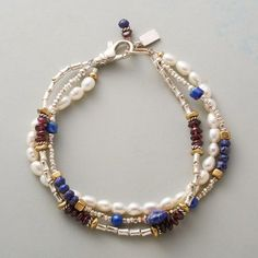 TRUE COLORS BRACELET Lapis, garnet and plump freshwater pearls show their true colors in a triple-strand bracelet with brass and sterling accents. Sterling silver lobster clasp. 14kt gold ring.