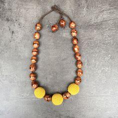 Rhonda - Ketting Handgemaakte ketting met bruine kralen. Afgewerkt met gele gehaakte bollen.  Al onze juwelen hebben een vrouwennaam meegekregen. Dit juweel noemt Rhonda.