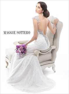 A sparkling Swarovski crystal V-back completes with beaded lace wedding dress.