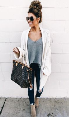 White cardigan over gray top and black distressed denim jeans.