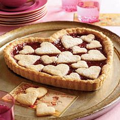 Show off your sweet side with this irresistible #tart made with an #almond sugar cookie dough crust that's spread with raspberry jam and topped with heart-shaped sugar cookies. perfect for valentines day!