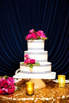 A beautiful white & navy detailed cake adorned with pops of pink flowers