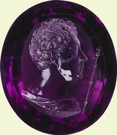 Intaglio of George IV    c.1820-30    Rundell, Bridge & Rundell    Presented to King George V by Queen Mary, Christmas 1927. Oval faceted amethyst engraved with a bust of George IV (1762-1830) in profile to the right. He is bare headed and wears classical drapery around his shoulders. A sceptre is shown to the right of the King's head. Signed in reverse below drapery: R . B & R . F t., (for the Royal goldsmiths, Rundell, Bridge and Rundell from 1797 to 1840).