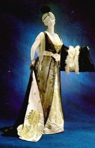 """Another 1912 worth evening gown. This one features a brocade underskirt with train. The overbodice and skirt are of black chiffon or georgette. Note the """"V"""" inset on this gown as well–a popular look in 1912, it seems. Good choice, ladies!"""