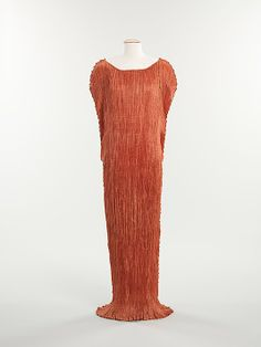 'Delphos' | Mariano Fortuny (Spanish, 1871-1949) | Date: ca. 1930 | Materials: silk, glass | The Delphos, Fortuny's signature gown, is a column of finely pleated fabric that draws its shape from the Greek 'chiton', particularly as depicted in the classical statue 'The Charioteer of Delphi' | The gown achieves its graceful draping with the help of strands of Venetian glass beads attached at the sides, which act as weights | The Metropolitan Museum of Art, New York