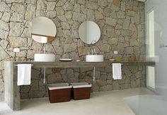 No banheiro da suíte principal, a parede revestida de pedra e a bancada de concreto bruto compõem um encontro sofisticado, reforçados pelas cubas brancas e espelhos redondos. Beleza sem excessos na proposta de Enrico Benedetti para uma casa no litaral paulista