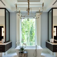 Kahn Design Group | chandelier, baseboards, espresso finished wrap around cabinetry/mirrors, gorgeous freestanding tub