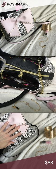 Betsey Johnson Bow Bucket Handbag w/ Crossbody Betsey Johnson Bow Bucket Handbag with Detachable Crossbody Strap | Black Spotted with White and an adorable Light Pink Gold Tone Studded Bow. All Hardware is Gold Tone. Zipper has a heart shaped tag with Betsey's Signature Xs & Os. Crossbody Strap is reversible, with Black on one side and light pink on the other. Floral Print Inside Lining. 3 Separate Compartments. Center is zipper closure; Two outer are magnetic clasp. Has inner zipper pocket…