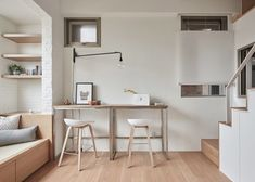 The 22m2 apartment in Taiwan features two wooden tables arranged like a bar, although they can also be configured as a rectangular dining table that juts into the room.
