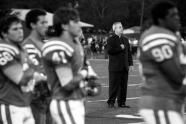 """Fr. Richard C. Hermes, S.J. listens to the National Anthem before the game against Plant on Sept. 1, 2012 at Jesuit High School. Fr. Hermes goes on the field before each game to say a prayer and then stays on the sidelines throughout the game. """"There are two times I approach a player on the field,"""" Hermes said. """"If they are injured or they feel bad if they made a bad play or not playing enough."""