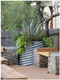 Galvanized steel container garden with gravel paths and arbors