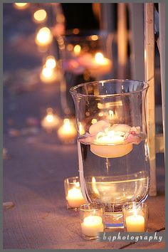 Candlelit Aisle DIY... You can get these vases at the dollar tree and floating candles at Ikea? Could be cute for setting up an area at the beach or?
