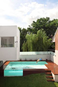The Devoto house . . .Cool above ground pool w/ plexi-glass side. I like the stairs built into the grass slope, & the wood deck.