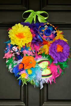 "Our unique ""Fiesta Feather"" Wreath is the most unique and festive fiesta wreath you will find. Full of a variety of plush feathers in many bright colors, and adorned with a fun sombrero hat, mexican paper flowers, an indian doll, and a sarape - this Fiesta wreath is bursting with flavor! This wreath measures approximately 18"" in diameter"