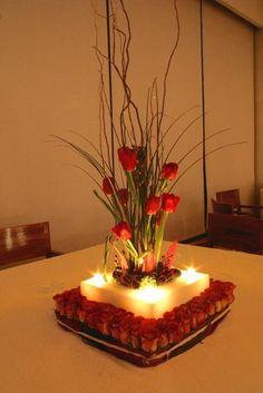 Composición floral con base de parafina y velas. Facebook.com/velasgamma