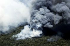 A helicopter drops water as bushfire smoke rises at Springwood in the Blue Mountains - ABC Sydney - Australian Broadcasting Corporation