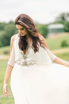 Wedding dress by Jenny Packham with plunging neckline, open sleeves and jeweled details. Image by Vue Photography.
