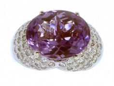 A gorgeous ring that makes a bold statement with a huge 16mm x 13mm oval shaped amethyst that weighs 10.40 cts. The amethyst is accentuated by 80 pave' set round brilliant cut diamonds that have an es